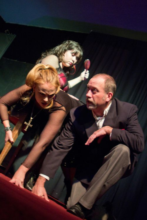Darcy (Justine Hince) spanks Ilona (Brigette Erpelding) as The Minister (Tony Bevile) looks on